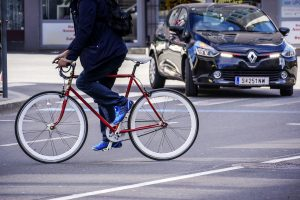 Ein Radfahrer quert vor einem Auto die Straße.